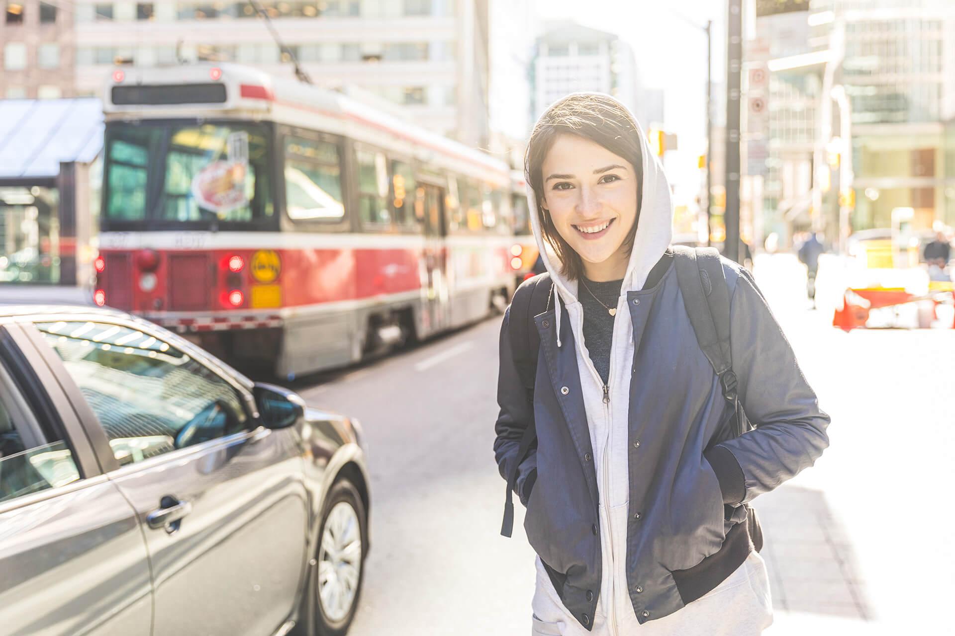 Image d'une jeune femme vêtue d'un chandail à capuche et d'une veste en denim, souriant en arrière-plan.