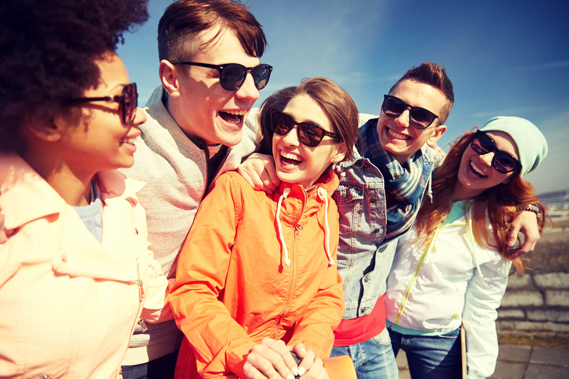 Image of five people with their arms around each other. Everyone is wearing sunglasses and laughing.